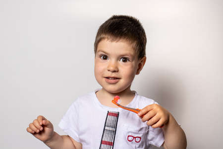 A little boy holds an orange toothbrush with toothpaste. The child brushes his teeth, prevention of tooth decay Reklamní fotografie