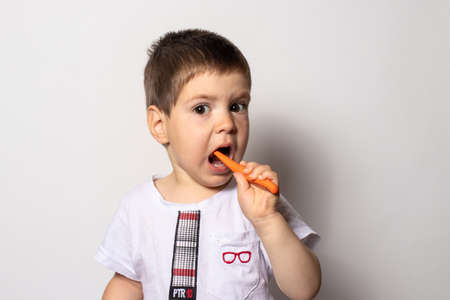 Little boy brushes his teeth with baby toothpaste. Childrens toothbrush.