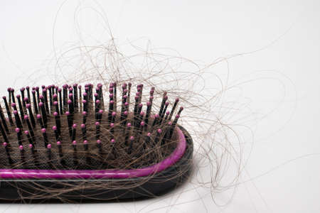 Hair loss on a comb on a white background. Baldness.