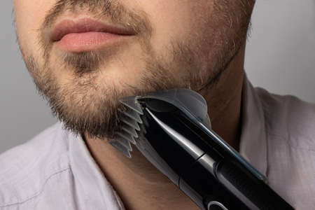 A man shaves his beard with a trimmer razor. Modeling beard, masculine style, facial hair care, morning routines in the bathroom