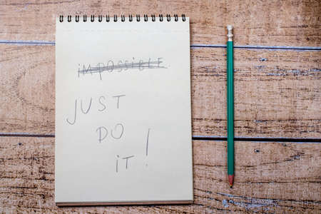Notepad and pencil, inscription Just do it. Quote about success and goal achievement in business and life