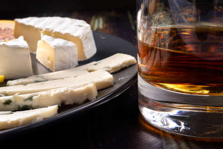 Whiskey in a glass and an appetizer for whiskey (blue cheese and Camembert cheese). Appetizer for alcohol, dear spirits.