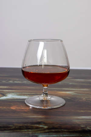 Glass with cognac on a wooden background. Dear elite alcohol.