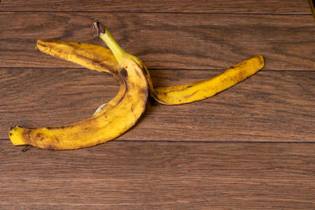 Banana peel of an overripe banana on a brown wooden background.