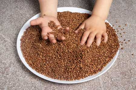 A child plays with buckwheat. Games for the development of fine motor skills of children, games with various cereals.