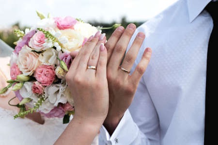 Hands of the bride and groom on the wedding day. Golden wedding rings