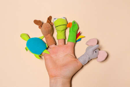 Fingers toys made of fabric on the hand on a beige background. Fingers Theater Stockfoto