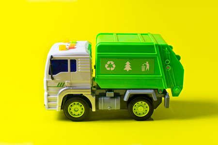 The toy garbage truck white-green with a yellow background. Children's toy car with buttons