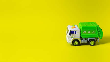 The toy is a garbage truck green with a white body on a yellow background banner with a place for text for a toy store. Children's toys typewriter