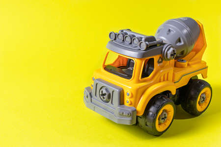 Orange concrete mixer toy typewriter on a yellow background. A banner with a place for text for a toy store. Copyspace.