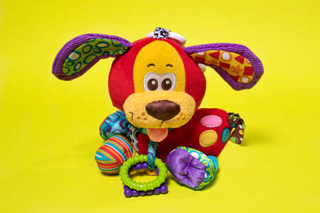 Red orange doggy toy on a yellow background. Soft plush toy for baby dog banner for toy store 写真素材