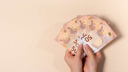 A man holds a lot of 50 euro banknotes in his hands. A banner with a place for text. 写真素材