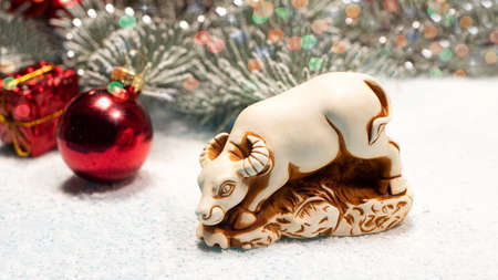 The bull on the white New Year's background is the symbol of 2021. With spruce branches and festive balls in the snowy background