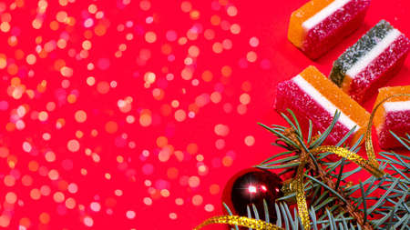 Marmalade and spruce twig with a ribbon and a toy on a red background. A banner on a red background with a place for copyspace text