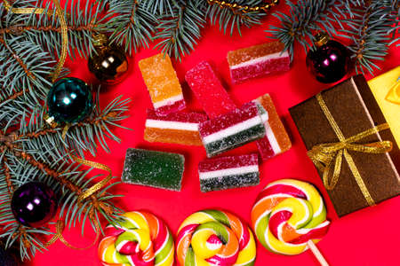 Leneds on a stick and marmalade on a red background. Banner for confectionery with Christmas decorations.