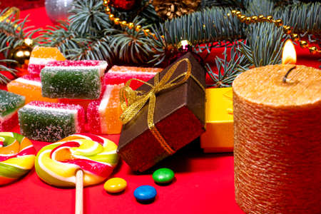 Leneds on a stick and marmalade on a red background with a burning candle. Banner for confectionery with Christmas decorations. Gifts for New Year