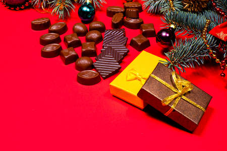 Gifts for Christmas chocolates on a red background. Delicious and sweets for children and adults. A banner for a confectionery with a place for copyspace text. 写真素材