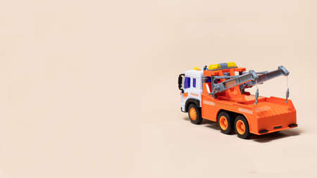 Toy orange tow truck on beige background banner with space for text. Children's car for loading and transporting cars
