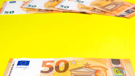 Fragment of the 50 fifty euro banknote on a yellow background. Close up currency money