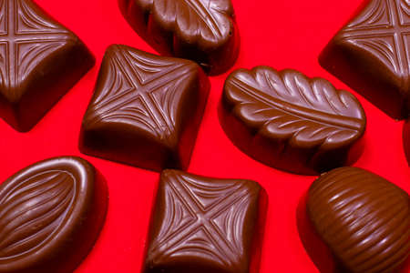 Chocolates made from milk chocolate on a red background macro-shooting close-up. Sweet food, sugar and cocoa. Sweet shop, pastry shop. 写真素材