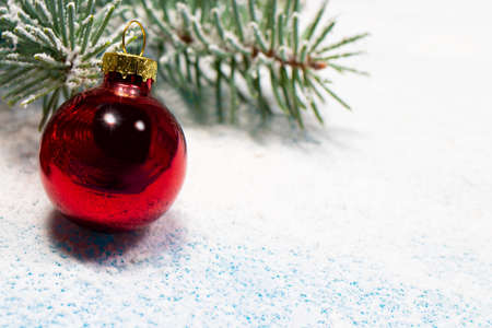 A red Christmas ball and a snow-covered Christmas tree branch on a snowy white background with a place for copyspace text. New Year 2021, holiday card.