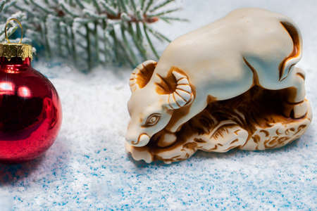 The symbol of 2021 is a bull on a white snow background with a red ball on a spruce branch. New Year's card for the holiday