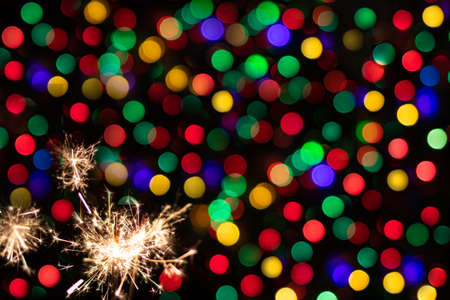 Sparkler on festive bokeh background. Festive greeting card for new year and christmas 2021, colorful lights in the background. 写真素材