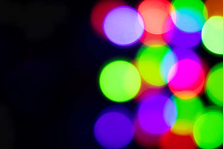 Multi-colored glares side on a black background with room for copyspace text. Festive New Year's background.