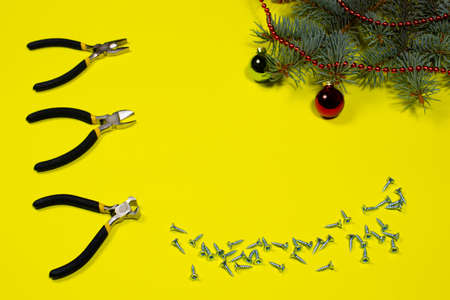 Construction tools pliers, rounds and self-cutters with a Christmas tree with a place to text on a yellow background. New Year's banner for a construction store 写真素材