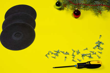 Cutting wheel for metal, screws and a screwdriver on a yellow background with a spruce branch. New year banner for hardware store and construction. 写真素材