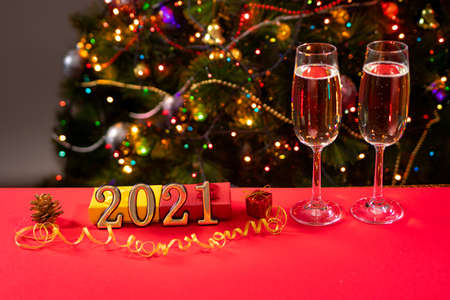 New Year's photo numbers 2021 and glasses on a red table with champagne on the background of the Christmas tree with lights and sides. Holiday and bull year.