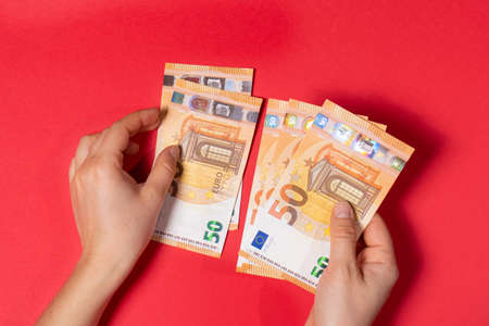 The man holds the money and counts the banknotes 50 euros on a red background. Banner for loans and loan money.