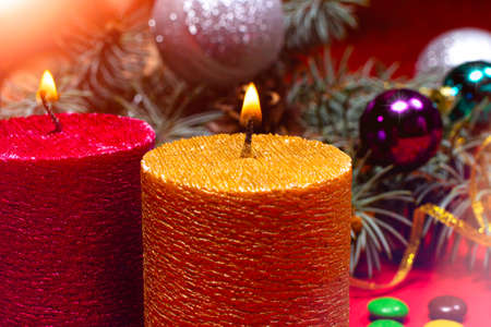A beautiful Christmas image - a burning candle in gold color against the background of the Christmas tree. Romantic holiday photo with bokeh. 写真素材