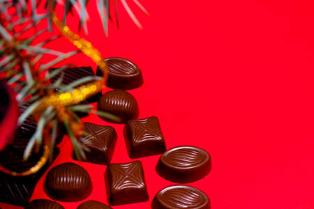 Chocolates on a red background with room for text. New Year's decor and chocolate - festive photo for confectionery