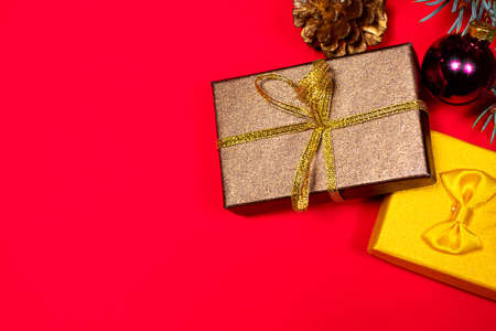Two Christmas gifts - brown and yellow, tied with ribbons under the Christmas tree on a red background. Gifts for New 2021 写真素材