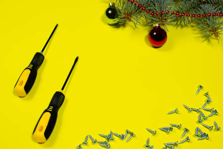 Screws and a screwdriver on a yellow background with a spruce branch. New year banner for hardware store and construction.