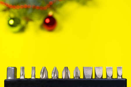 A set of nozzles for a screwdriver on a yellow background with New Year's decoration 2021. With a place for copyspace text