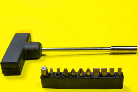 A set of screwdriver nozzles and a screwdriver on a yellow background with space for copyspace text. Tools for construction and repair shop.