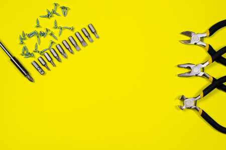 Screwdriver with set of nozzles, self-cutters and other inturments - pliers, cutters, tongs on a yellow background with space for text.
