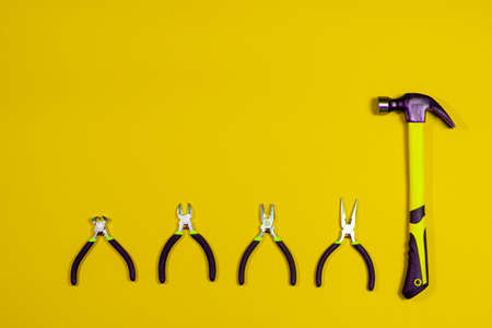 Clippers, pliers, tongs, rounds and hammer on a yellow background. Construction tools with a place for copyspace text. Repairing, building materials store.