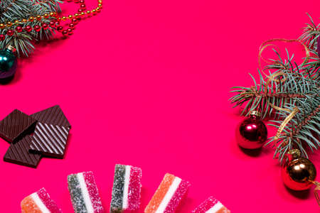 Marmalade jellies and spruce twig with a ribbon and a ball on a pink background. A New year banner for a pastry with a picture of chocolate with a place for copyspace text