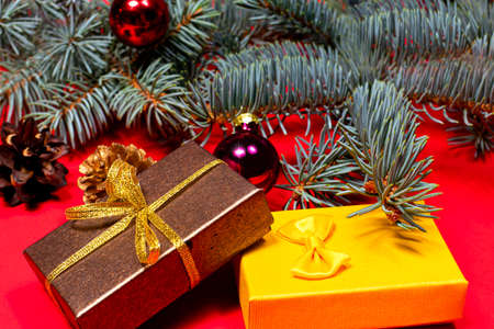 Two Christmas gifts - brown and yellow, tied with ribbons under the Christmas tree on a red background.