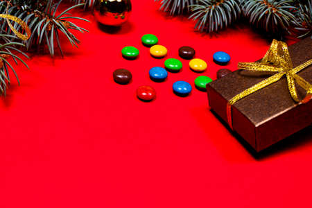 Multicolored lollipops and candies on a red background with Christmas decoration, gifts, ribbons and spruce branches. Banner for a confectionery pastry shop. 写真素材