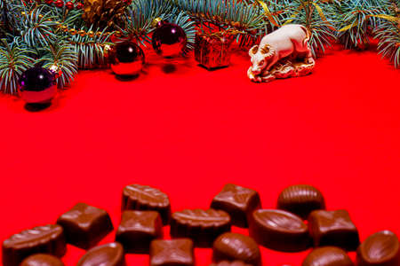 Chocolates on a red background - festive photo for confectionery