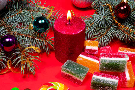 Marmalade on a red background with a burning candle. Banner for confectionery with Christmas decorations. Gifts for New Year 写真素材