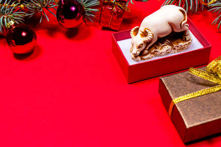 New Year's bright photo of a bull on a red background. A sprig of Christmas tree and a ball with a place for text. Copy space