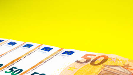 Fragment of the 50 fifty euro banknote on a yellow background. Close up currency money. Place for text. Cop