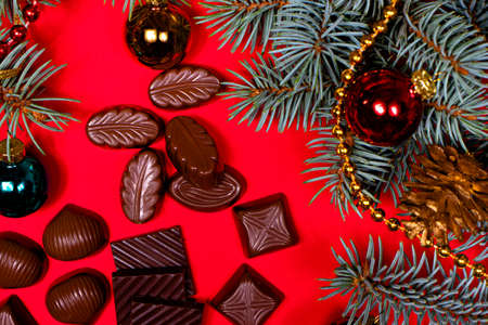 Chocolates on a red background. New Years 2021 decor and chocolate, candy - festive photo for confectionery.