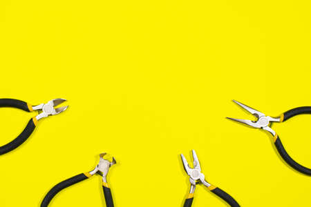 Tools on a yellow background - pliers, cutters, round-waterers to work with fittings and repair. A banner for a construction store. 写真素材