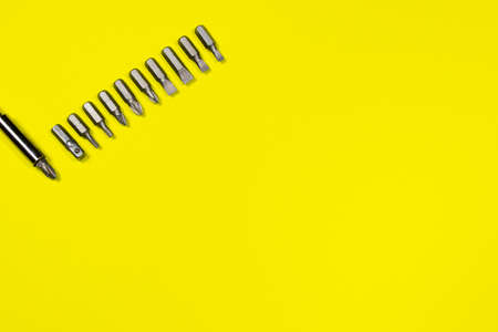 A set of screwdriver nozzles and a screwdriver on a yellow background with space for copyspace text. Tools for construction and repair shop 写真素材